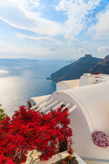 A view of caldera and sea from house roof decorated with red flowerrs in Firostefani village, Santorini island, Greece