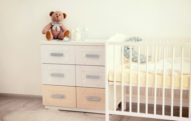 Modern interior of light baby room with crib and chest of drawers