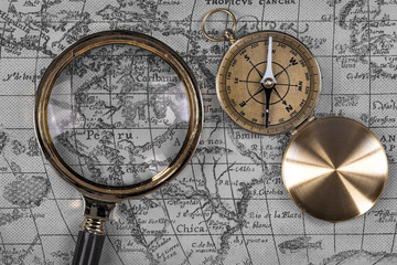 top view, vintage marine compass and magnifier on old map, close-up