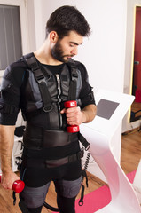 Handsome bearded man working out with weight on electro muscle stimulation EMS