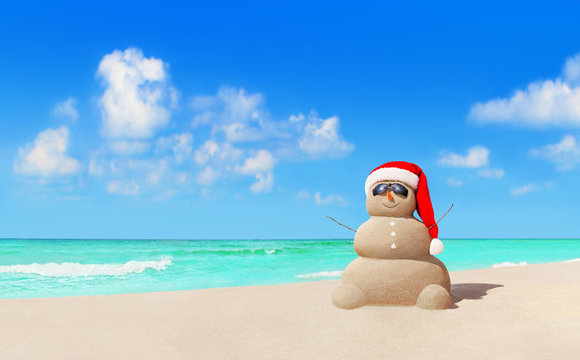Sandy snowman in Christmas Santa hat and sunglasses at beach