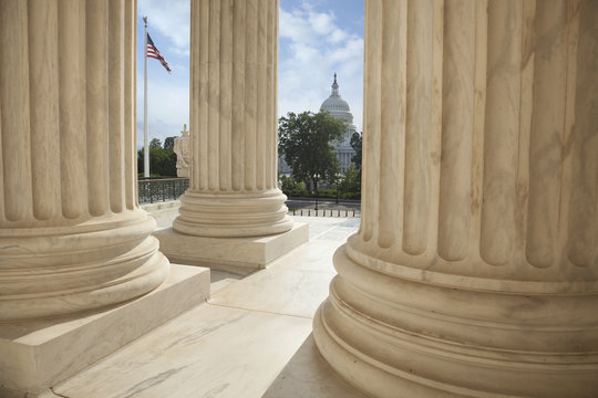 Columns of the Supreme Court with an American flag and the US Ca