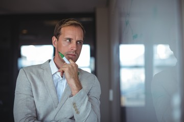 Thoughtful businessman looking at whiteboard