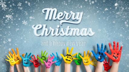 """viele angemalte Kinderhände mit Smileys vor Winter-Hintergrund mit """"Merry Christmas"""" Nachricht"""
