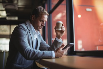 Businessman using mobile phone while having coffee