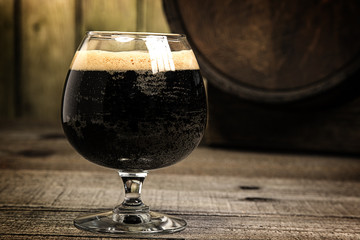 Russian Imperial Stout in snifter glass on wood background and b