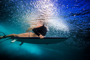 Slim blonde girl in bikini a surfer with surf board duck diving underwater under ocean reflected surface. Family lifestyle, people sea water sport lessons and beach swimming activity