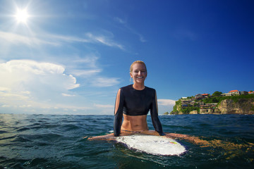 Surfing girl sitting on surfboard in the ocean water. A sport model smiling under sunlight and waiting for a swell sea surfing wave to start an action