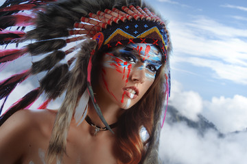 Indigenous woman with warpaint on face. Native american hat on pretty model. Closeup beauty portrait with creative makeup. A girl standing on mountain above the clouds.