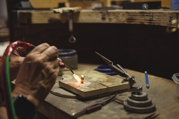 Hands of craftswoman using blow torch
