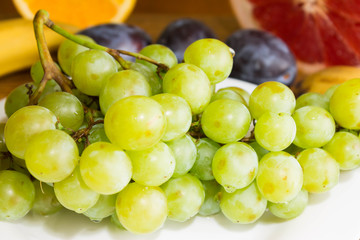 Green and black grapes in a white plate