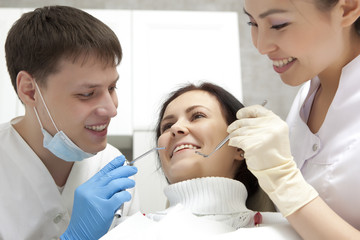 Stomatology concept - dentist with mirror checking patient girl