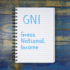 GNI- Gross National Income acronym written in notebook on wooden background