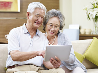 senior asian couple using a tablet computer together