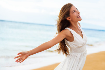 Wall Mural - Free happy woman on beach enjoying nature. Natural beauty girl outdoor in freedom enjoyment concept. Mixed race Caucasian Asian girl posing on travel vacation holidays in dress.