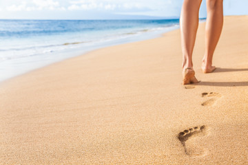 Beach travel - woman relaxing walking on sand beach leaving footprints in the sand. Closeup detail of female feet and legs on golden sand on Kaanapali beach, Maui, Hawaii, USA. Fototapete