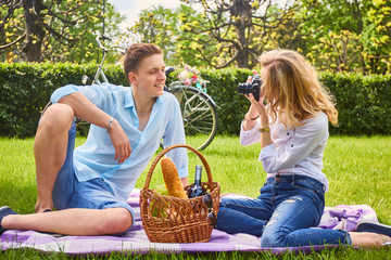 Blonde female photo shooting her boyfriend at picnic time.