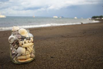 Seashells in jar on the sand beach. Tropical landscape with sea and white boats.