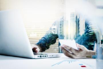Double exposure of businesswomen using smart phone with blur cit