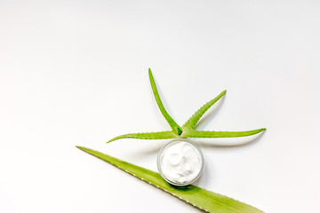 cream, aloe and wooden spoon on white backround top view