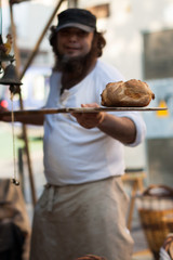 Fototapete - Man holds shovel on a loaf bread