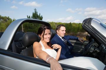 Happy bride and groom on their wedding car