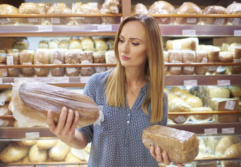 Woman selecting loaf of bread at supermarket