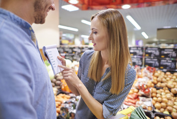 Couple double checking grocery list
