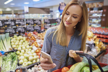 Woman using cellphone in grocery store