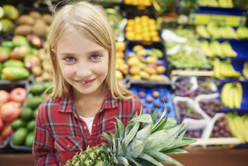 Pretty girl holding pineapple in supermarket