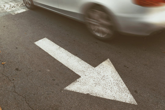 Driving car in wrong direction against traffic arrow sign