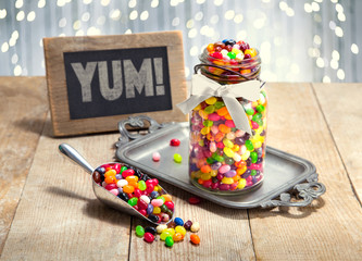 Yum sign next to candy filled jar and scoop of multi color assorted jelly beans on a party table