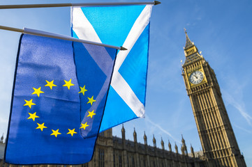 Scottish and EU flags flying in front of Westminster Palace and Big Ben under bright blue sky, London