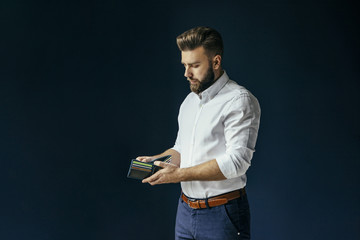 Young bearded businessman, dressed in a white shirt and dark blue trousers, standing and holding an open wallet with a credit card. In the background dark blue wall. A man looks into an empty wallet.