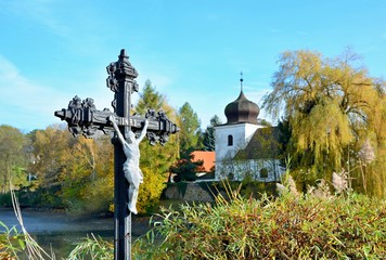 Jesus on cross outside in nature with church in background. INRI, Iesus Nazarenus Rex Iudaeorum