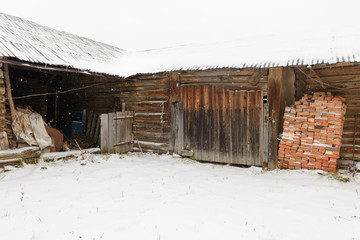 old abandoned wooden shed with a variety of subjects during a snowfall