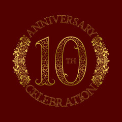 10th anniversary celebration vintage patterned logo symbol. Golden circular ornate emblem on red.