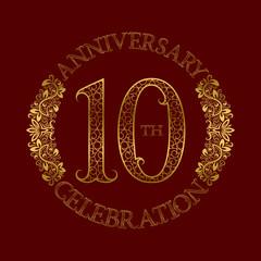 10th anniversary celebration vintage patterned logo symbol. Golden circular ornate emblem on red.