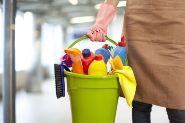 Woman holding cleaning supplies in building