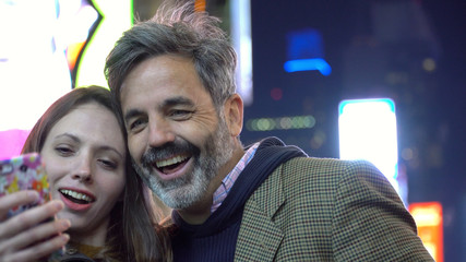 Young attractive couple take selfie photos with smart mobile cell phone in Times Square New York at night. Using bright advertisement billboards as background in Manhattan