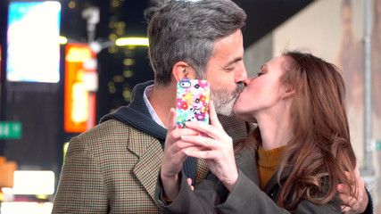 Young attractive couple on date night in Times Square New York City, Manhattan - taking selfie photo kissing with smart cell phone to share on social media for friends to tag and like.