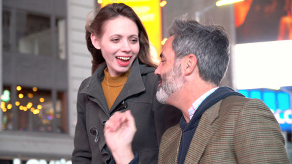 Young attractive couple on date night walk together talking and laughing. New York City, Times Square Manhattan in evening. Cold autumn weather wearing sweater and jacket
