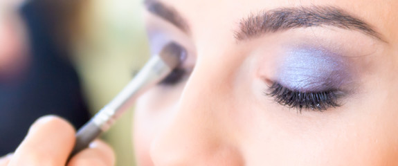 Girl doing make-up in a beauty salon.Focus on near eye. Shallow depth of field