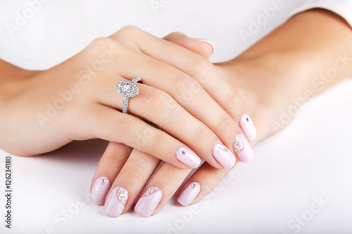 """Close up hands of young woman with engagement ring with a ..."
