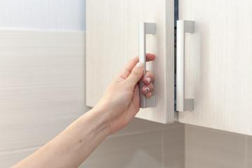 Fototapeta Female hand open the cupboard doors, close up obraz