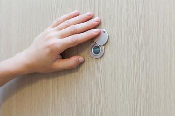 Hand near the door peephole on a new wooden door