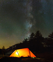 Red tent in a forest in the mountains, under the stars and milky way.