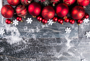Christmas background with decorations, red celebration balls on wooden board