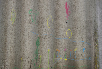 children's drawings in chalk on gray fence