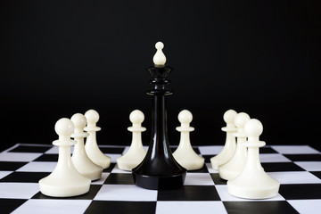 Chess king surrounded by enemy pawns. Captivity and defeat. Concept with chess pieces against black background